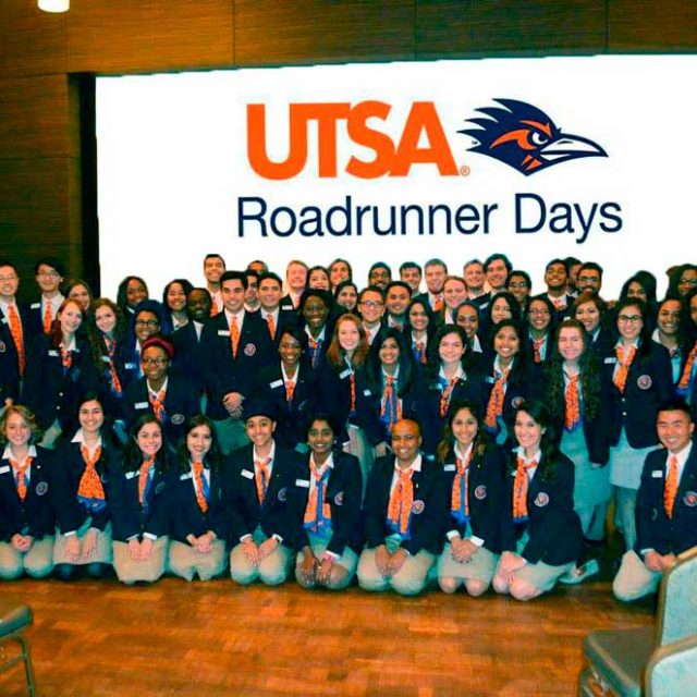 UTSA Ambassadors in front of screen with Roadrunner Days logo