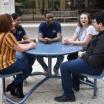 FYE Students sitting around blue table outside