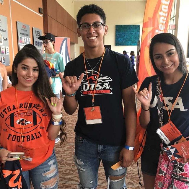 Three students wearing blue and orange UTSA T shirts standing in the HEB Student Union lobby