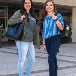 Two roadrunners with backpacks standing under Business School sign